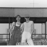 Black and white outdoor photo of Johnny Abush (right, in hat and sunglasses) with partner Chuck Grochmal (left, in overalls).