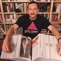 Colour photo of Johnny Abush in the Twice Blessed archive, standing in front of a bookshelf and behind a large opened catalogued binder.