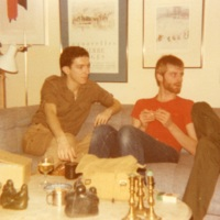 Johnny Abush (left) and Chuck Grochmal (right) sit on a sofa at home looking towards someone out of frame.
