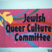 Magenta banner of the  Jewish Queer Culture Committee showing a yellow dove with multi-coloured ribbons trailing behind it.