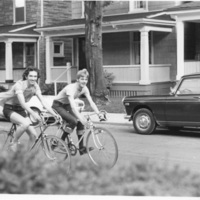Black and white photo of Johnny Abush (left) and Chuch Grochmal (right) riding bicycles down a street.